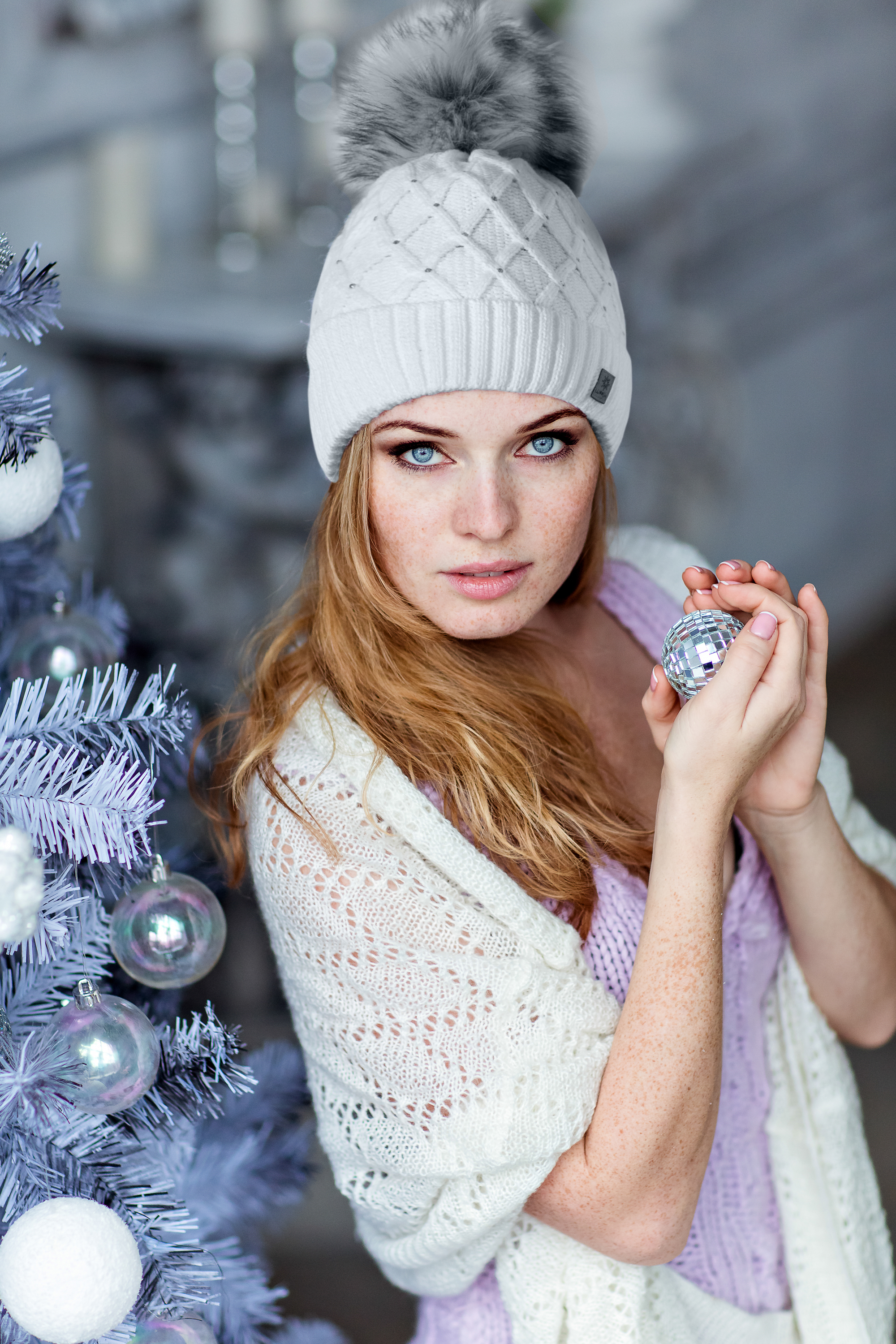 Very beautiful red-haired girl with blue eyes in a white hat costs about silver Christmas tree