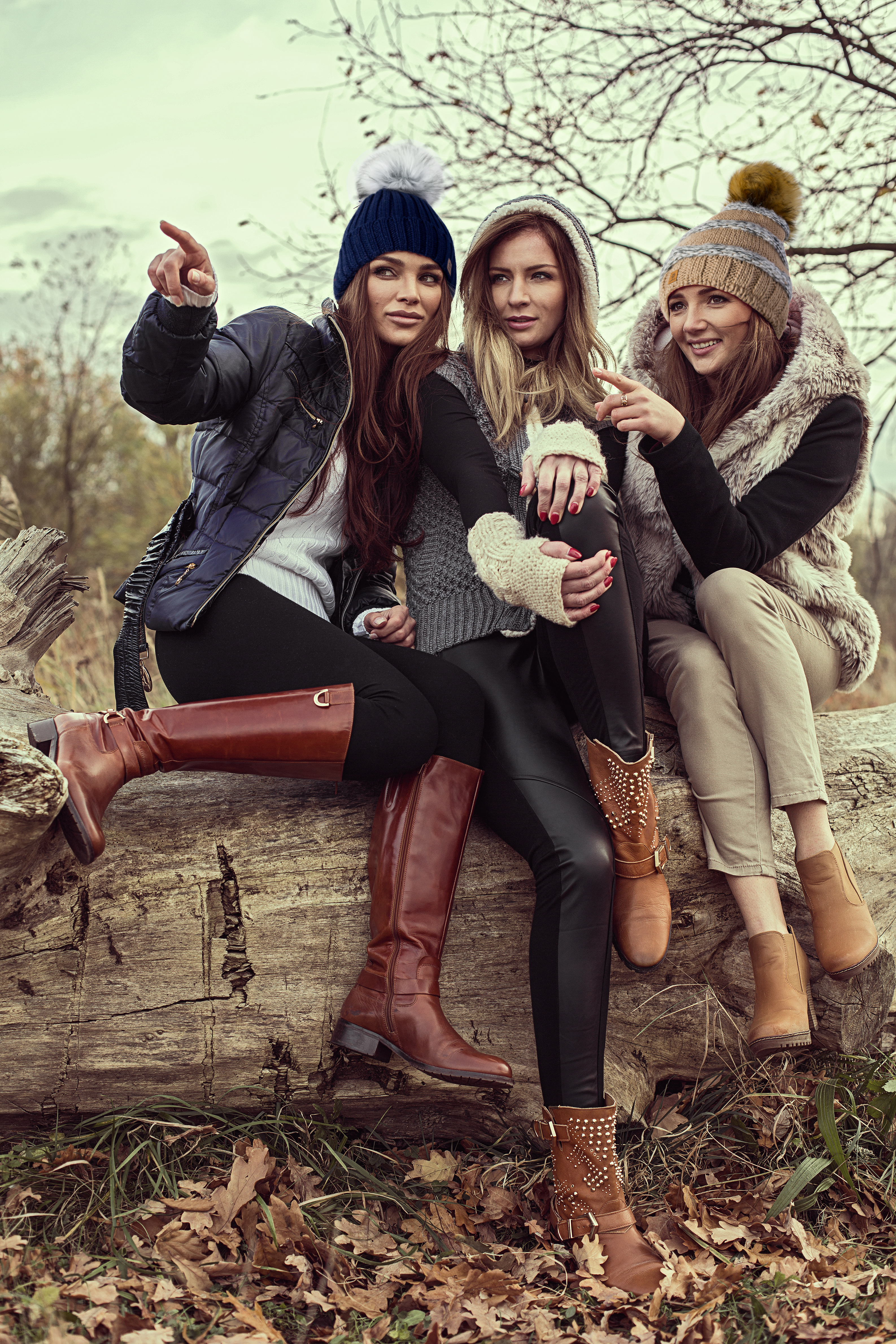 Happy tree girls wearing a woolly hats and showing something