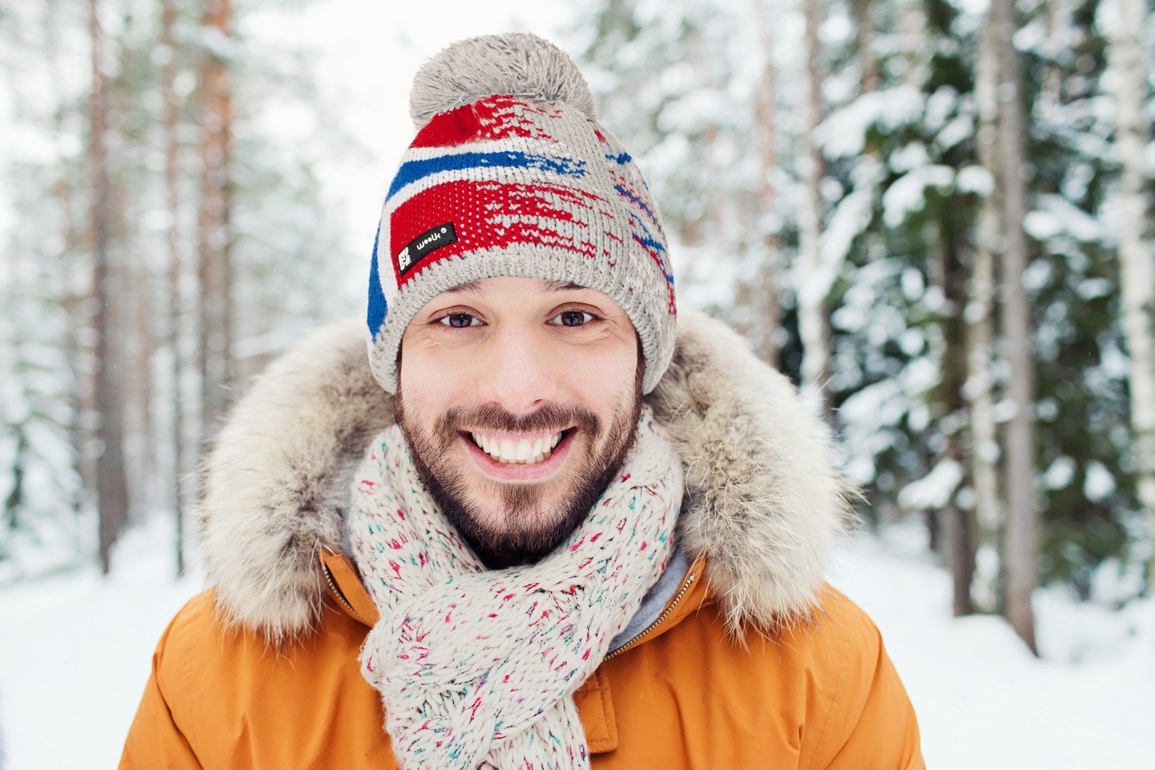 smiling young man in snowy winter forest